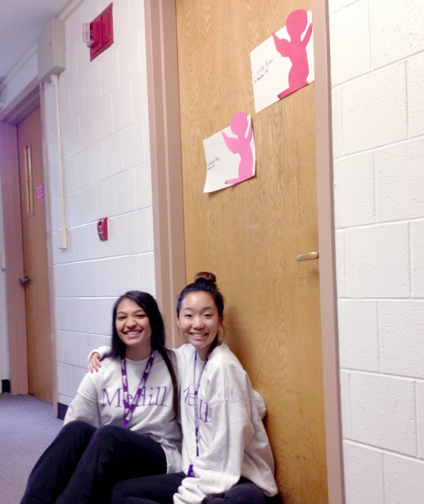 Natasha Roy and Lucia Kim in their Medill sweatshirts in front of their room. Photo by Angela Chon.