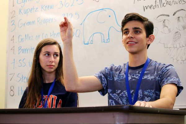 Male student makes a point at front of classroom with female student.