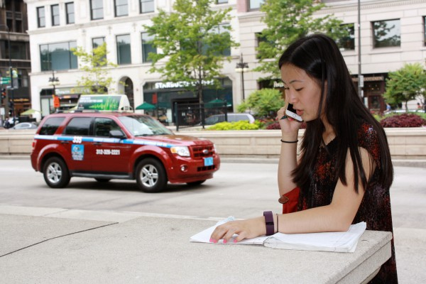 Katie Ho talking to a source over the phone during a field trip to Chicago. Photo by Caitlyn Rosen.