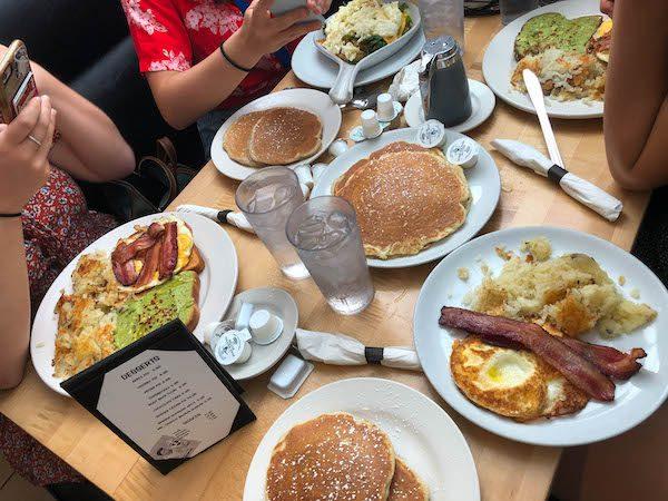 Seven plates of breakfast food