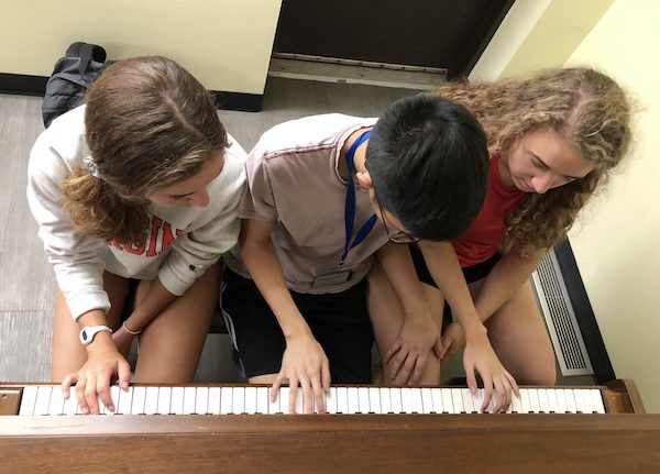 Overhead shot of three students play piano at the same time in the common room
