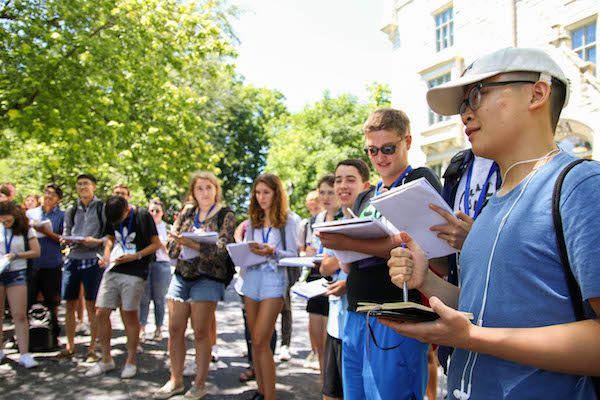 Male student stands next to other students outside and takes notes