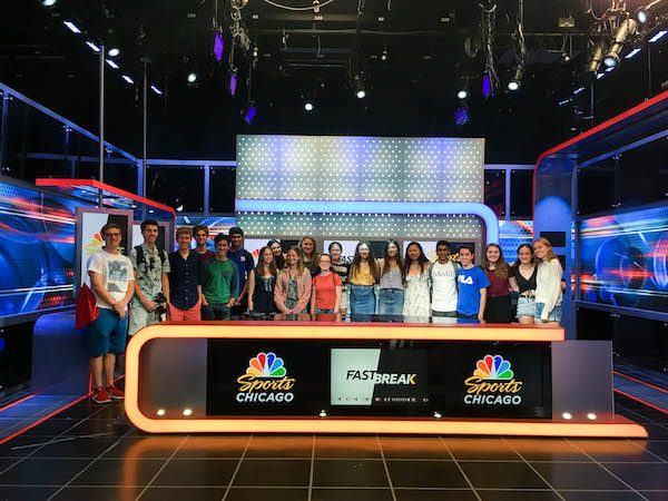 A group of students standing behind a broadcast desk