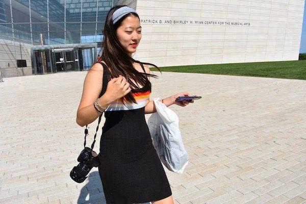 A girl in a black dress carries a camera as she walks through campus.