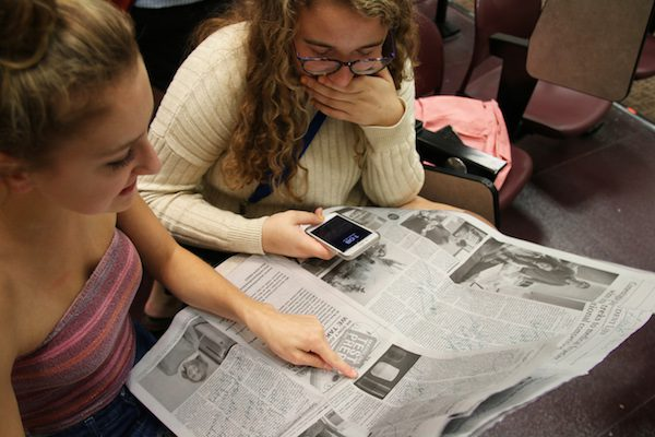 Two girls read the edits on their newspaper.