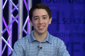 Boy sits at a Northwestern News Network broadcast desk.