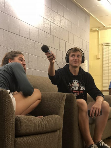 Male student holds up audio recorder while working on a project in dorm lounge while a female student sits next to him.