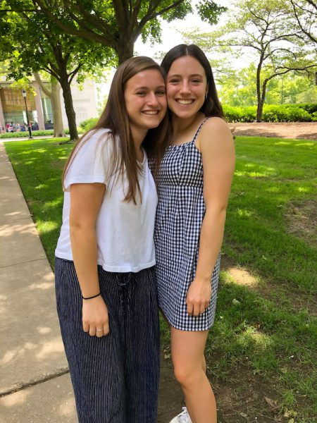 Two girls in white and blue take picture outside Fisk Hall.