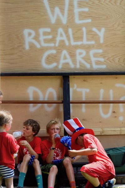 "Three boys and one girl in red T-shirts lean against the back of a float that says, ""We really care, don't you?"""