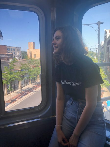 Girl sits on a window ledge on the train.