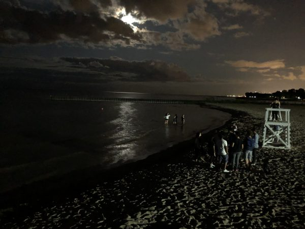 Students walk on the beach just after sunset