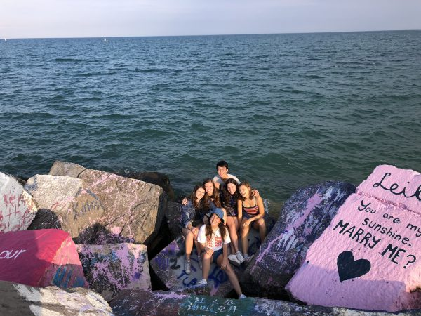 A group of teens sit on rocks painted with messages in front of a lake.