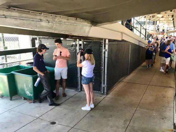 Two cherubs interview a male stadium staff member.