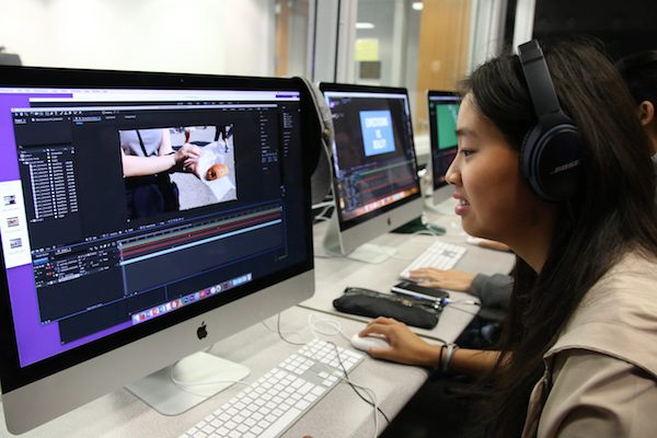 A girl edits her Adobe After Effects project on the computer.