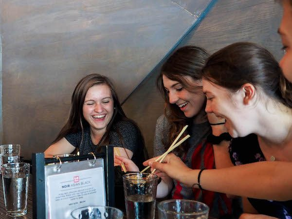 Four females smiling and sharing ramen