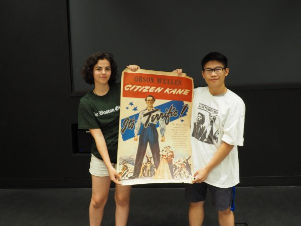 "Two students hold up an old poster for the Orson Wells movie ""Citizen Kane."" The poster is animated with bright colors and says ""It's Terrific!"" across the middle."