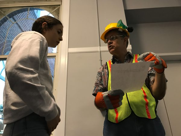 Man dressed in constructionwear speaks to a young girl about her paper.