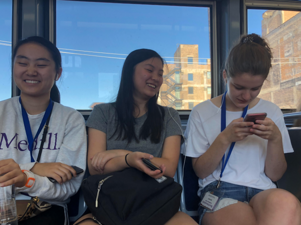 Three female students sit on the train and laugh. Two are sharing headphones.