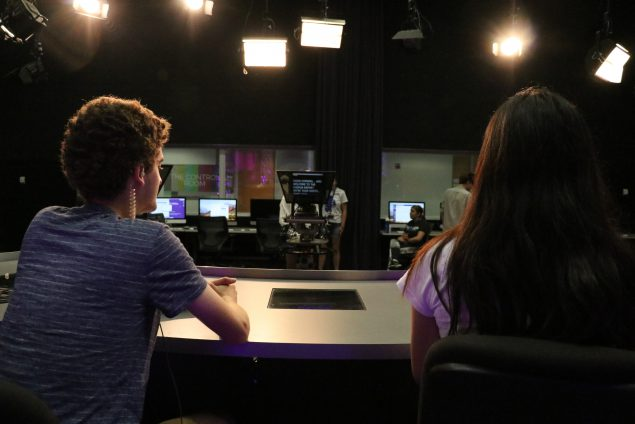 Two students sit at the news anchor desk before a broadcast.