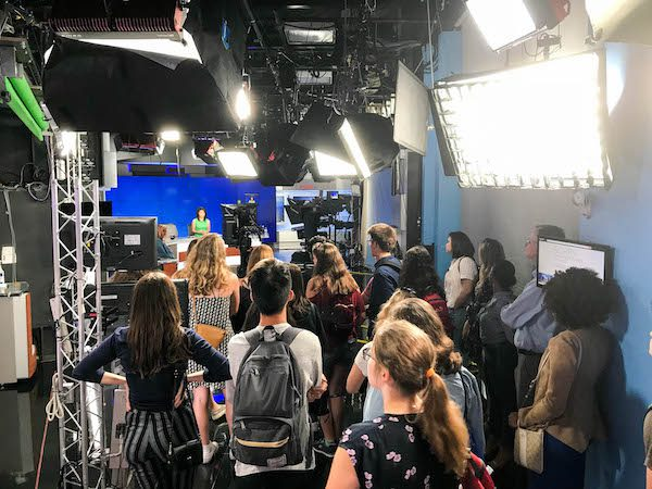 Students look at an anchor sitting behind a broadcast desk