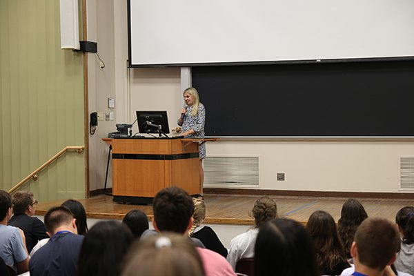 A woman presents slides on a podium in front of journalism students.