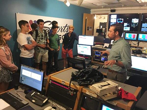 A man presents a TV broadcast room to a group of journalism students.