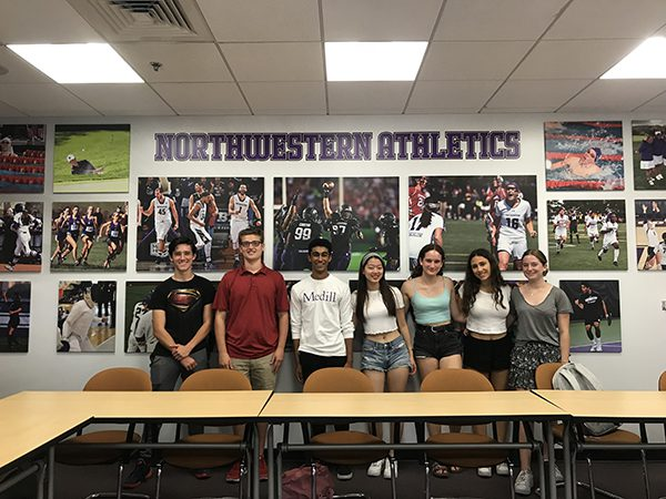 Journalism students pose for a picture at athletics communications in front of a wall of sports photos.