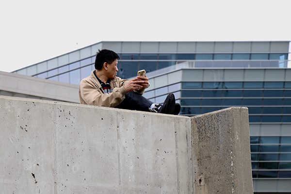 A man sits on a rooftop holding his phone.