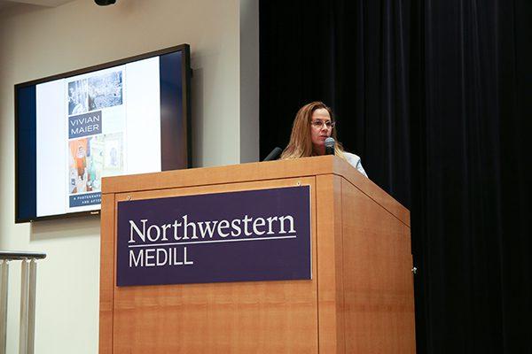A woman presents slides at a podium.
