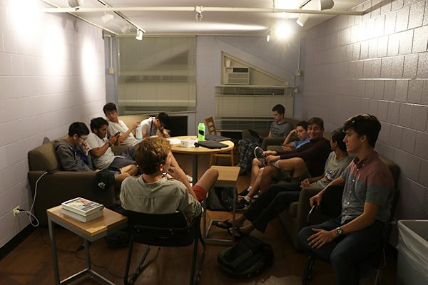 A group of 10 male cherubs sit in their dorm lounge and socialize late at night.