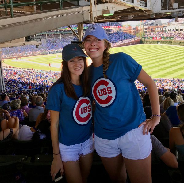 Two students pose for a photo in Cubs shirts at Wrigley Field.