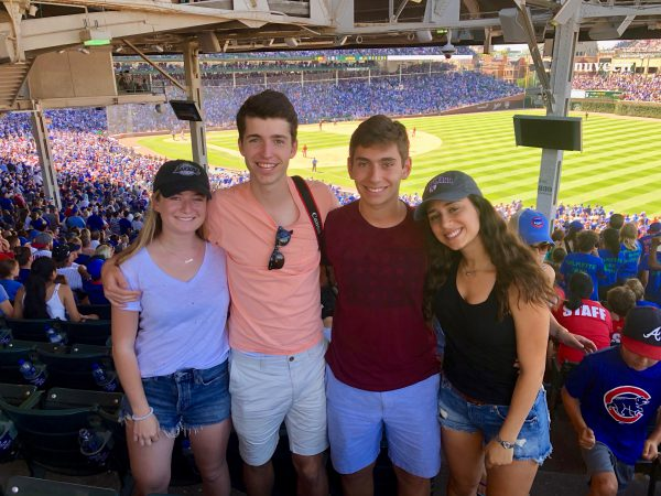 Four students pose for a photo in front of the baseball diamond at Wrigley Field.