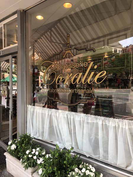 "The exterior of Patisserie Coralie with a sign on the window glass that says ""Patisserie Coralie, fabrication artisanale"""