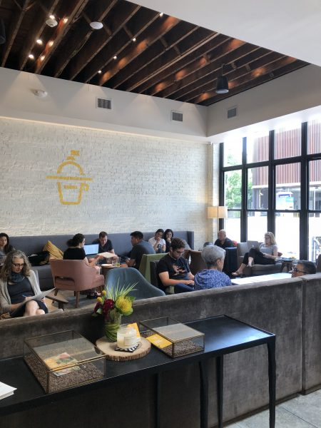 Interior of Cupitol cafe in Evanston with people sitting on couches and arm chairs. There is a window on one wall and a white brick wall in the back with a yellow Cupitol logo painted on it.